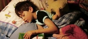 little boy sleeping overnight in bed