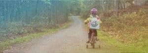 child riding bike down path